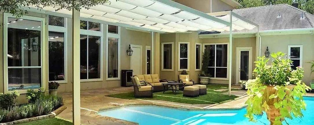 Home with pool and white retractable fabric canopies
