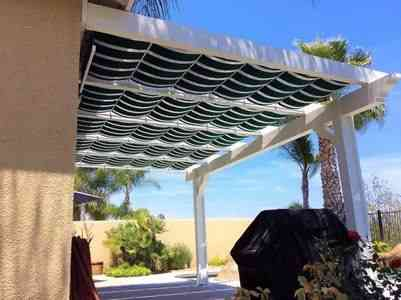 White pergola on patio with green striped awnings