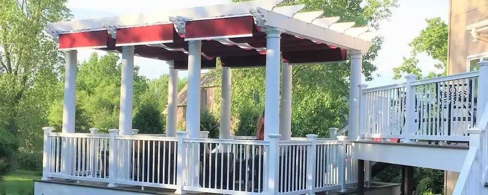 White backyard pergola with red fabric retractable canopies