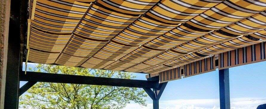 Striped fabric retractable canopies over patio