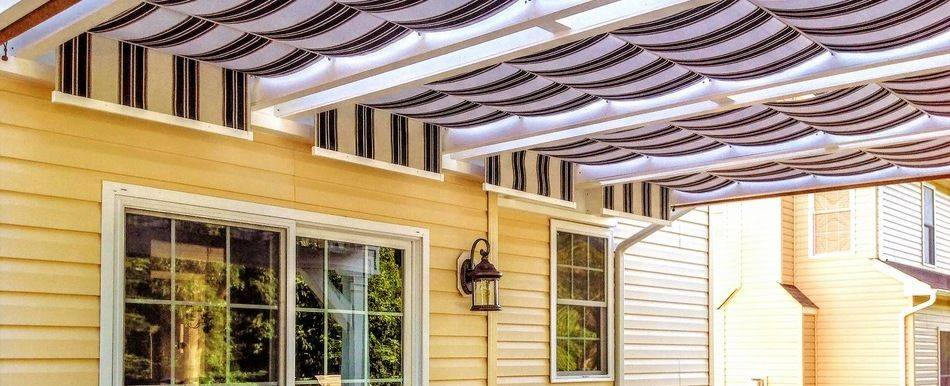 Striped fabric retractable canopies over backyard patio
