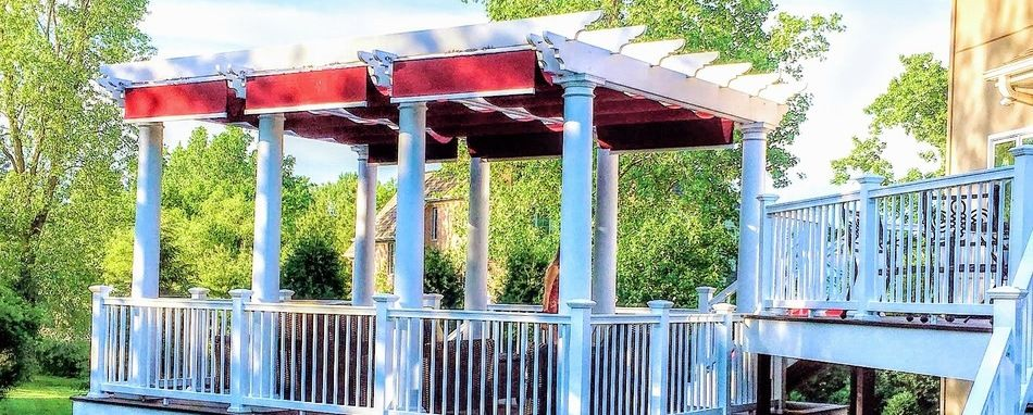 White backyard pergola with red burgundy fabric retractable shades