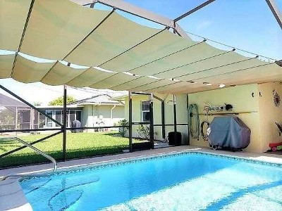 Fabric shade runner over swimming pool