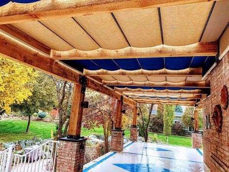Fabric retractable canopies on slide wire over patio